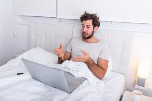 Man lying in bed on virtual call